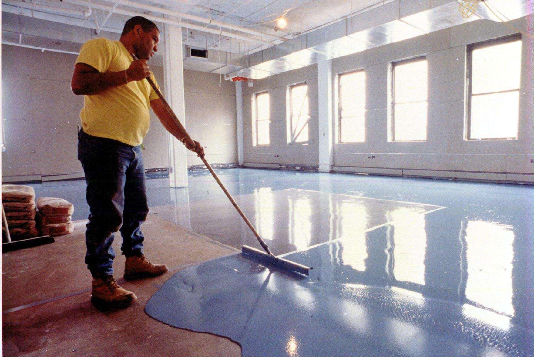 ... Man In Yellow Applies Blue Epoxy Paint To Basement Floor